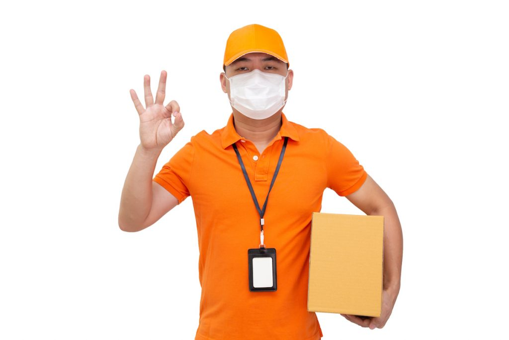 Delivery man holding parcel box and wearing protective mask and giving the OK sign with his fingers