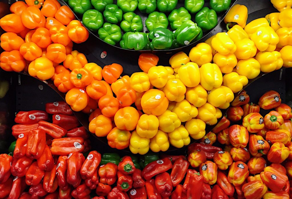 Fresh, colorful peppers in produce bins at store.