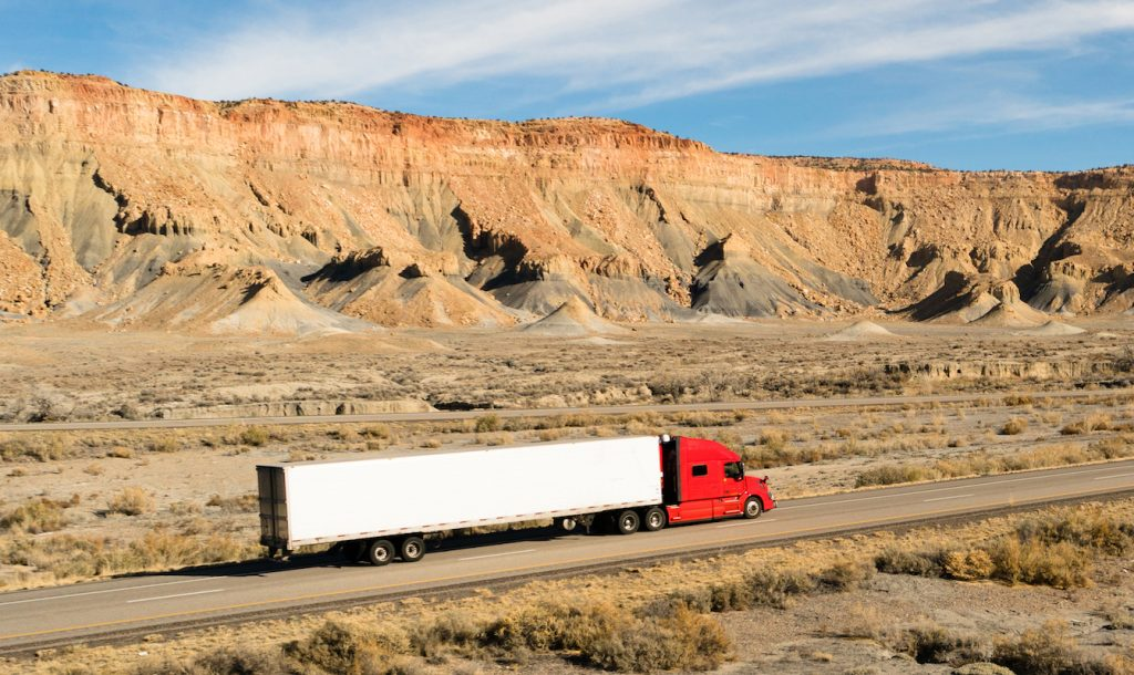 A big rig on Utah highway surrounded by mountains.